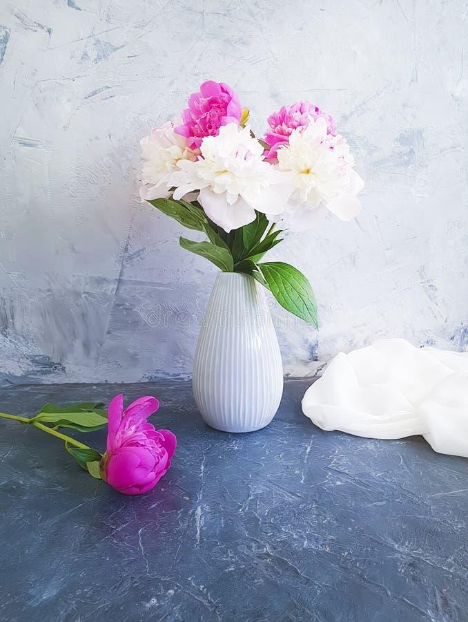 Vintage de la flor de la peonía en un compositionon del florero un fondo concreto gris foto de archivo libre de regalías