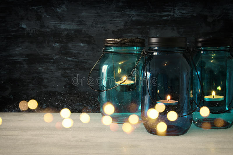 vintage decorative magical mason jars with candle light on wooden table royalty free stock photography