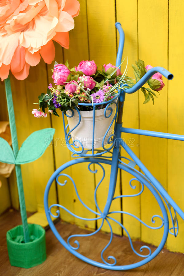 Vintage decorative metal blue bicycle flower-stand with pink peonies stock photo