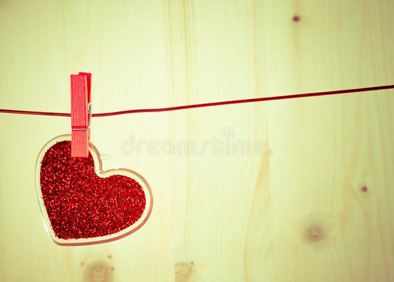 Vintage decorative red heart hanging on wood background, concept of vintage valentine day stock photography