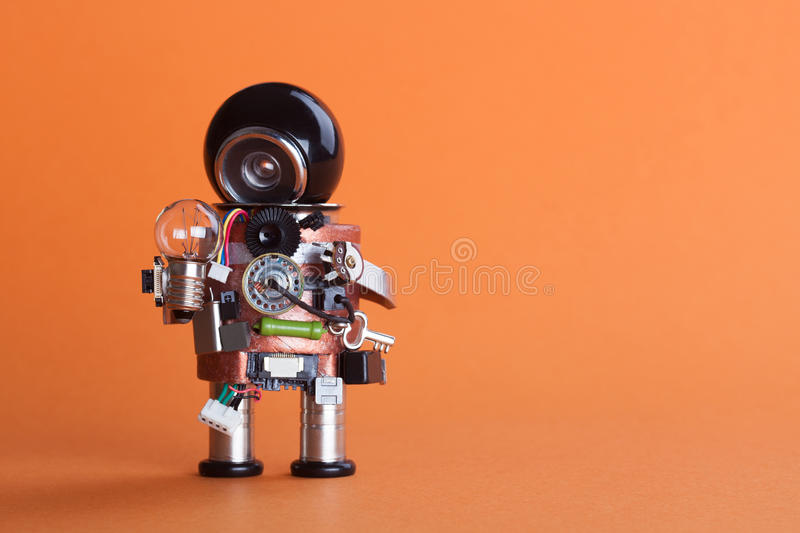 Vintage design robot character with lamp bulb. Circuits socket chip toy mechanism, funny black helmet head. Copy space, orange. Retro design robot character with royalty free stock photography