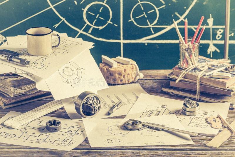 Vintage designer desk of mechanical parts on green chalkboard background stock images