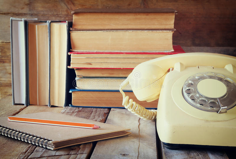 Vintage dial phone, phone book next to stack of old books over wooden table. vintage filtered image stock image