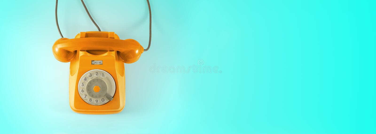 A vintage dial telephone with blue background. A orange vintage dial telephone with blue background royalty free stock image