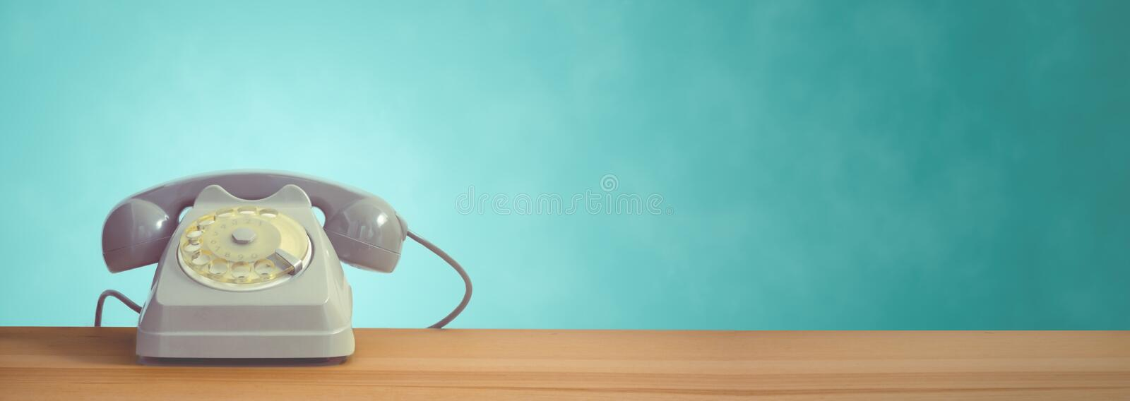 A vintage dial telephone with turquoise background. A grey vintage dial telephone with turquoise background stock photos