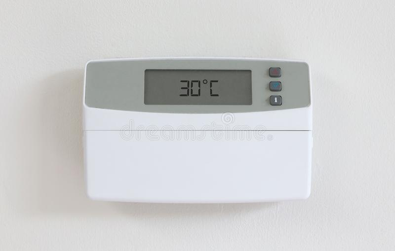 Vintage digital thermostat - Covert in dust - 30 degrees celcius. Vintage digital thermostat hanging on a white wall - Covert in dust - 30 degrees celcius royalty free stock photo