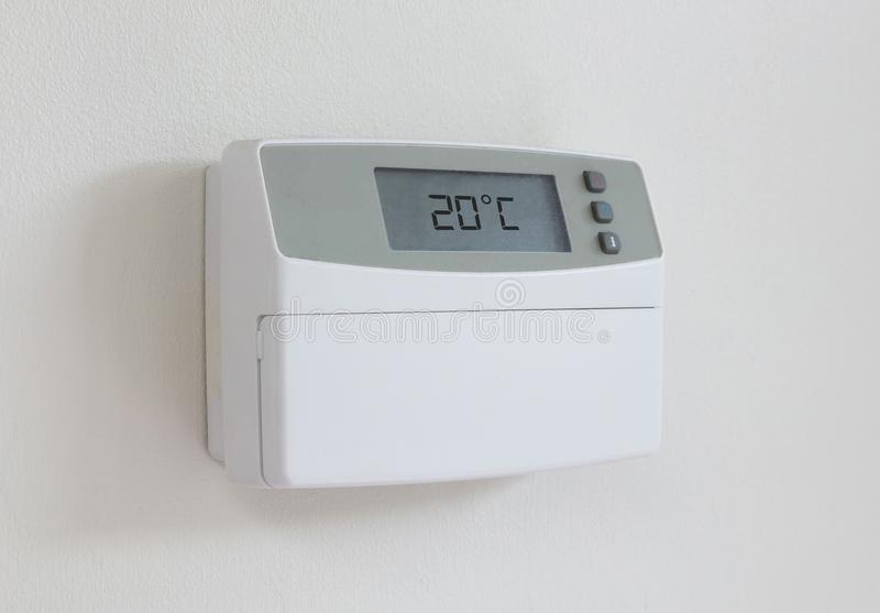 Vintage digital thermostat - Covert in dust - 20 degrees celcius. Vintage digital thermostat hanging on a white wall - Covert in dust - 20 degrees celcius stock image
