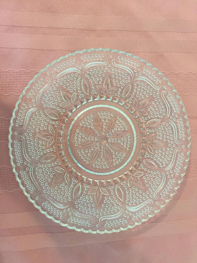 Vintage Dinner Plate with a floral center. Vintage glass dinner plate. Dinnerware from the 1930`s through the 1950`s. Floral pattern. Clear glass. Scalloped edge stock photo