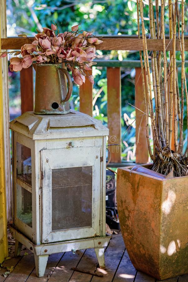 Collection Of Dirty Old Furniture And Plants On A Vintage Wooden Verandah. Vintage and dirty furniture, pot plants and artificial flowers in a metal jug sitting royalty free stock photos