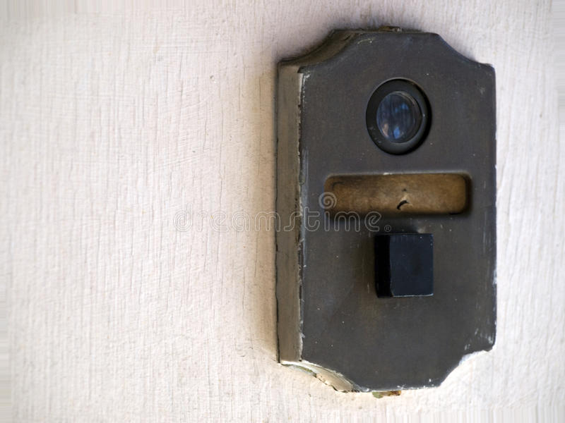 A Old Door Bell Mechanism With Peep Hole To See Through On A Old White Door.