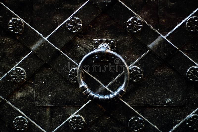 Vintage door handle on a black iron door with forged products, concept of authentic objectsn stock images
