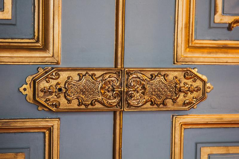 Vintage door hinges painted patterns covered with gold leaf close-up. luxury fittings in the interior royalty free stock image