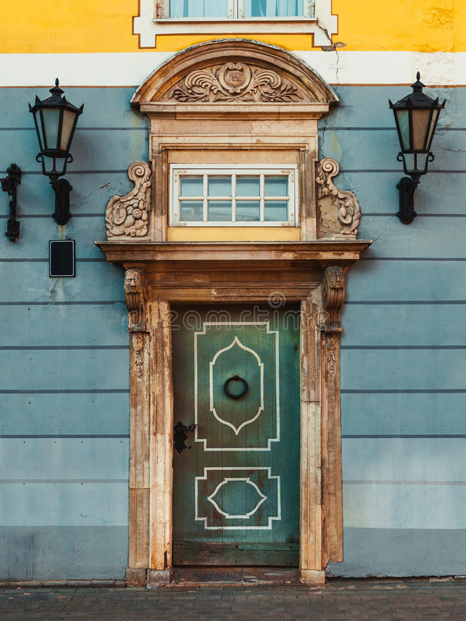 Vintage door on a old building facade with retro lamp. In old Riga city, Latvia stock photo