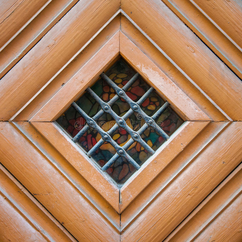 Vintage door spyhole with stained glass window and grid. In an old door of wood stock photos