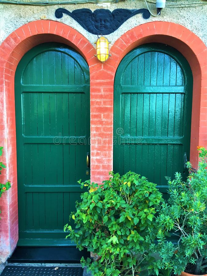Vintage doors and beauty in Brown Castle, Portofino village, Genoa province, Liguria region, Italy. Colours, entry, angel, decoration, green, greenery, plants royalty free stock photo