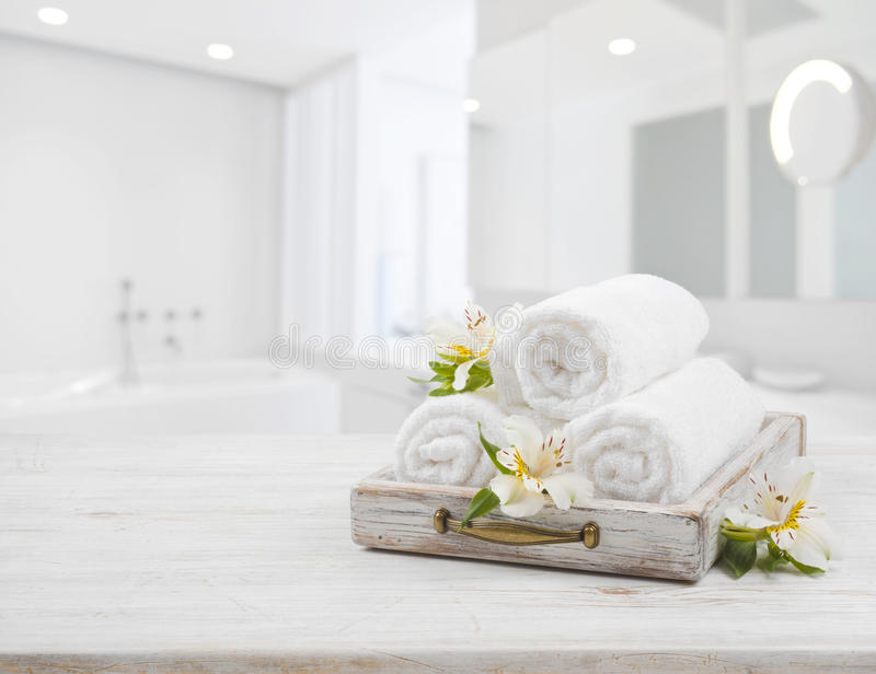 Vintage drawer, spa towels and orchid flowers over blurred bathroom stock photography
