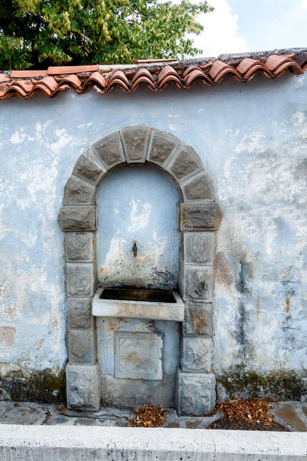 Vintage drinking water fountain in Smartno, Goriska Brda, Slovenia. Niche in brick wall, stone arch above water tap royalty free stock images