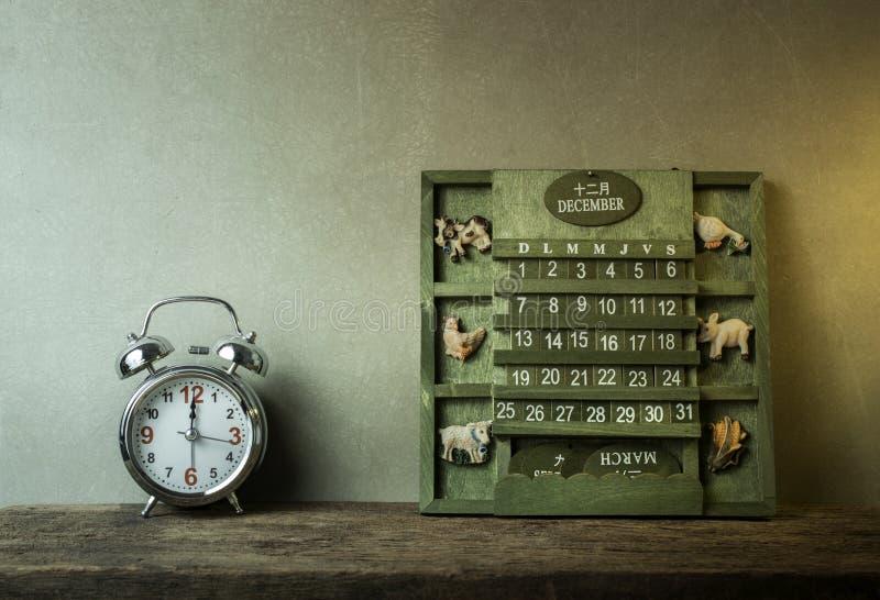 vintage e despertador de madeira verdes do calendário no fim de madeira da tabela de imagens de stock royalty free