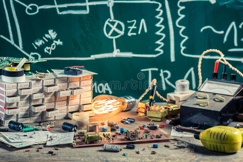 Vintage electronics components in physics lab. On old wooden table stock image