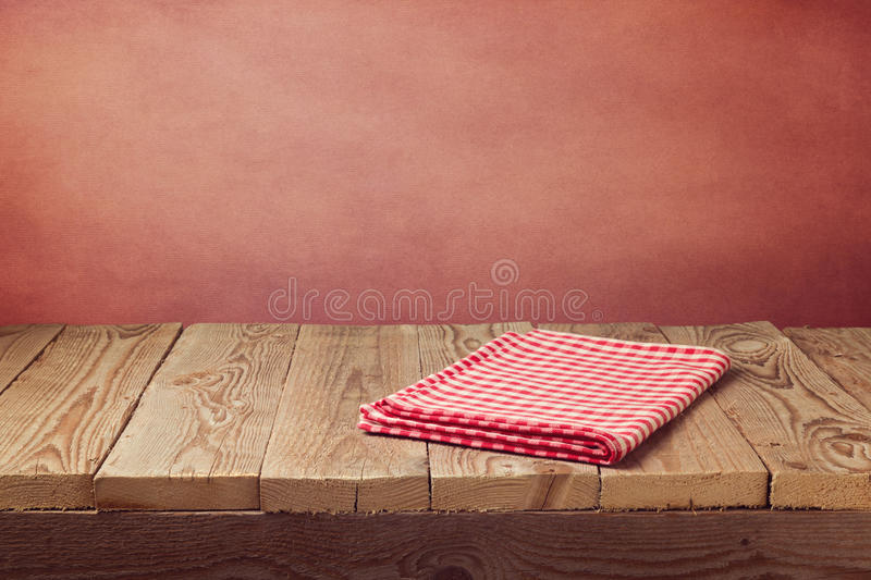 Vintage empty wooden deck table with tablecloth over grunge red background. Perfect for product montage display. Vintage empty wooden deck table with tablecloth stock image