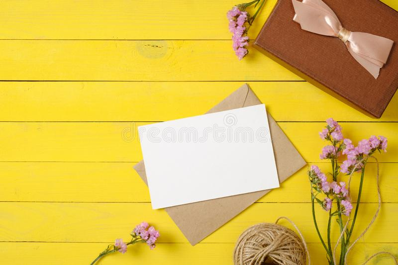 Vintage envelope with blank card, purple flowers, tag, gift box, ribbon bow on yellow wooden table. Wedding invitation card royalty free stock photos