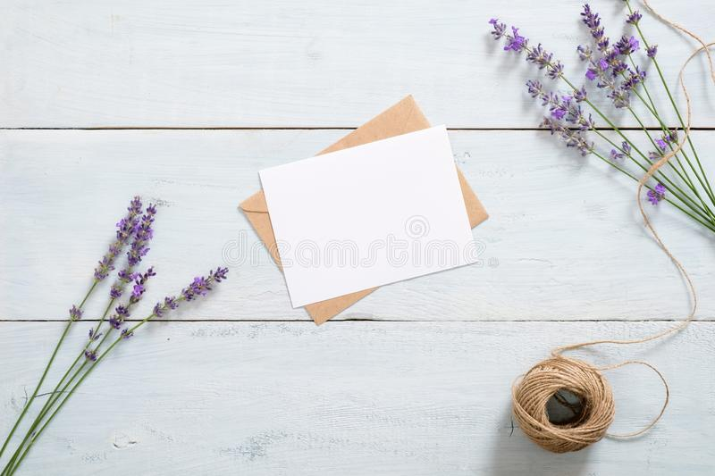 Vintage envelope, blank paper card, lavender flowers and twine on rustic blue wooden background. Romantic composition, love love royalty free stock photography