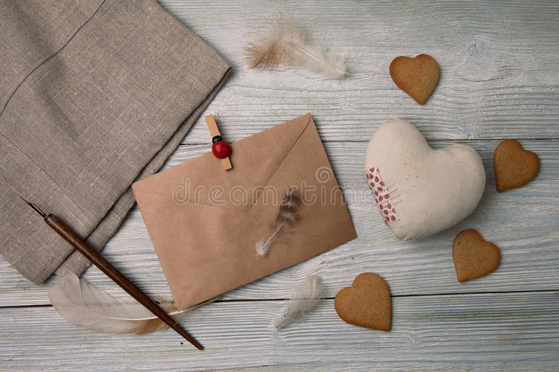 Vintage envelope with cookies. Happy Valentine`s day concept. Gingerbread cookies with vintage envelope and soft shape heart, writing love letter. Festive royalty free stock photos