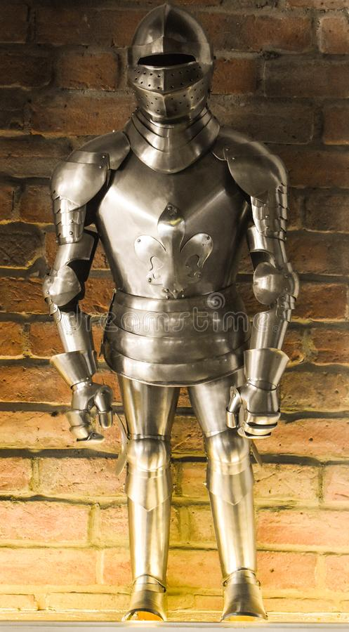 A vintage european full body armor suit against the brick wall background stock photography