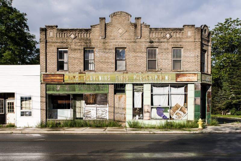 Vintage, farmácia abandonada com o tijolo de Brown do blefe e telhas verdes da porcelana foto de stock