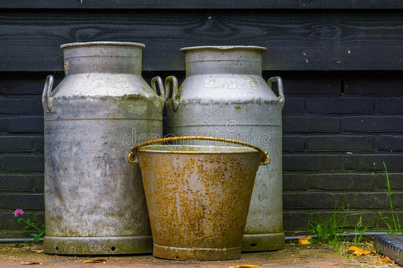 Vintage farm equipment, metal milk cans and a old rusty bucket, agriculture background. A vintage farm equipment, metal milk cans and a old rusty bucket royalty free stock photo
