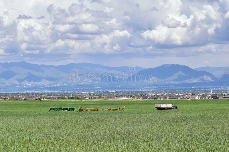 Vintage Farm Truck and harvest machinery with Panoramic view of Wasatch Front Rocky Mountains, Great Salt Lake Valley in early spr stock photography