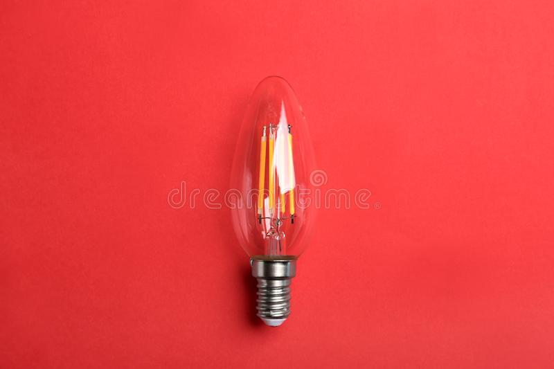 Vintage filament lamp bulb on red background royalty free stock photo