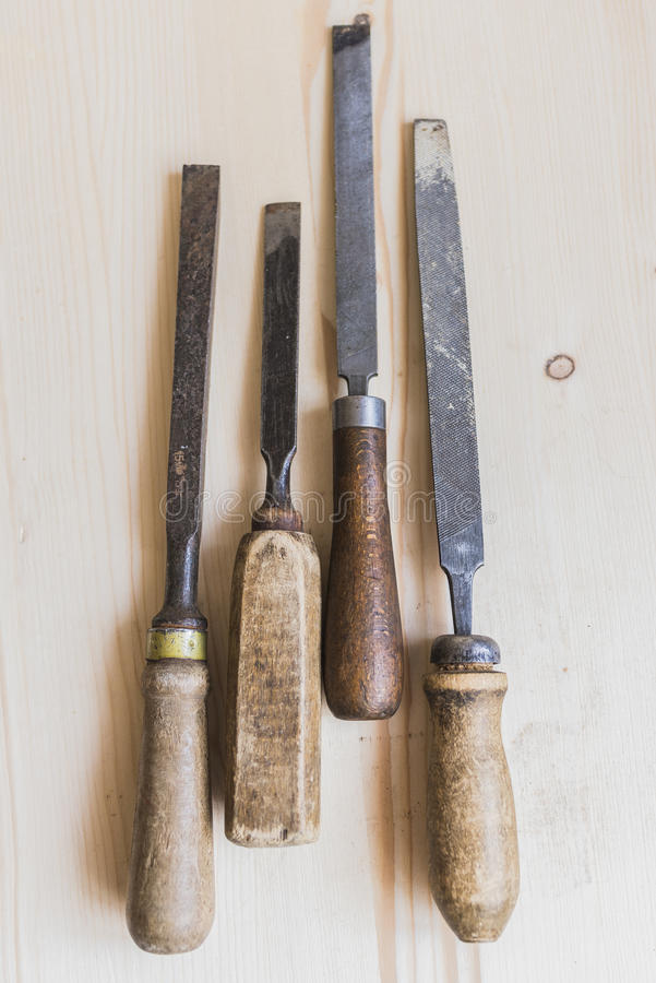Vintage files and chisels 7. Old vintage files and chisels with shabby handles lying in a row one after another on a light wooden table.Man`s tricks concept royalty free stock photo