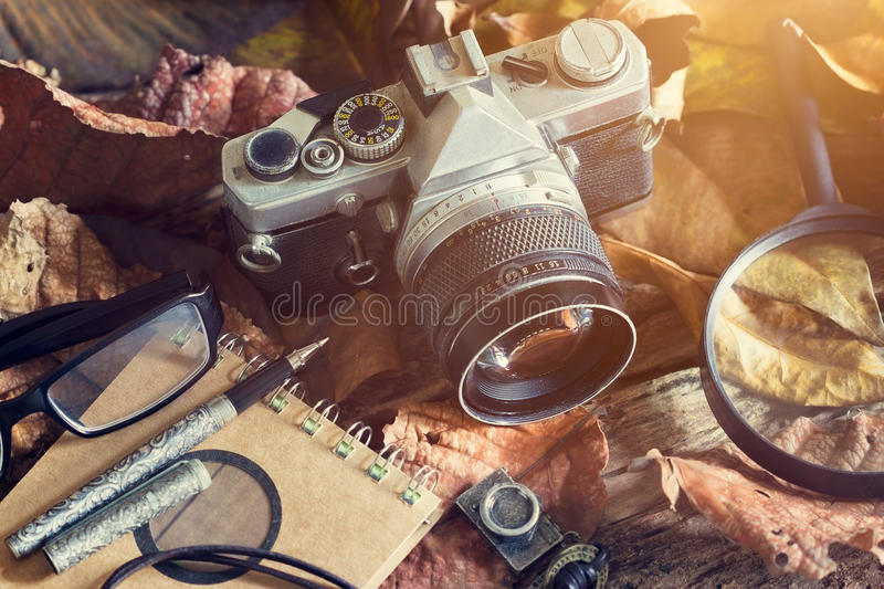 Vintage film camera with dust on dry leaf and wooden in nature. Vintage film camera with dust on dry leaf and wooden in natural background, Vintage color tone royalty free stock image