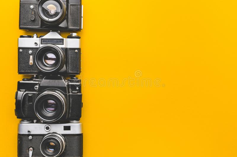 Vintage Film Cameras On Yellow Background Surface. Creativity Retro Technology Concept stock photos