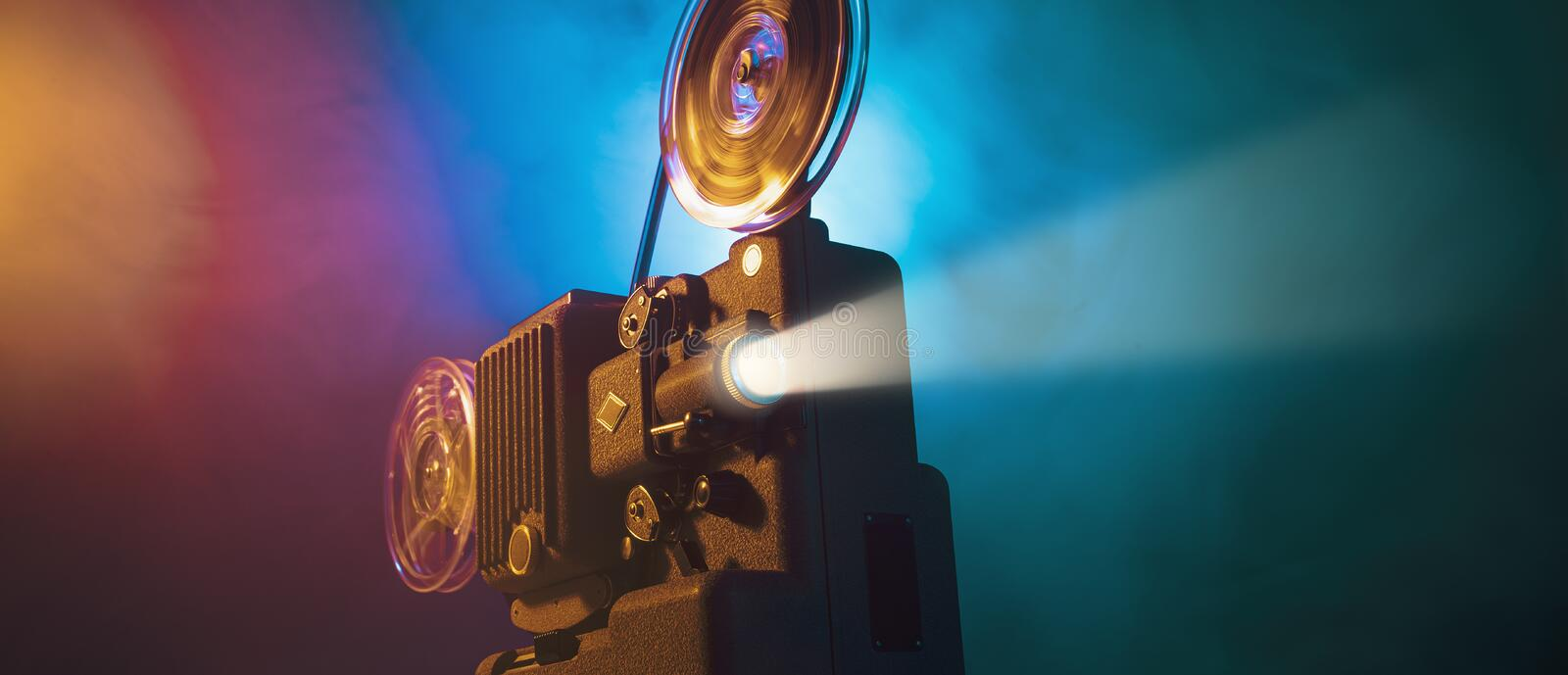 Vintage film projector and film screening. Vintage old fashioned projector in a dark room projecting a film, cinematography concept stock images