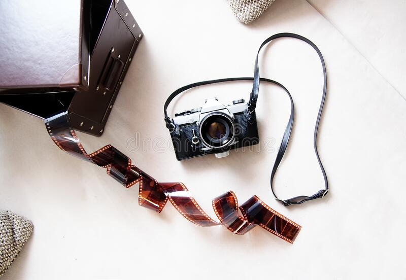 Vintage film rangefinder camera with leather case and photographic film on light colored background. royalty free stock images