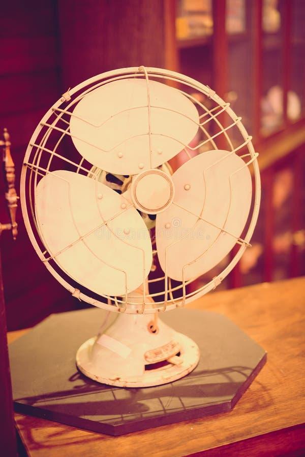 Vintage filter: Vintage fan on wood table in old shop stock photo