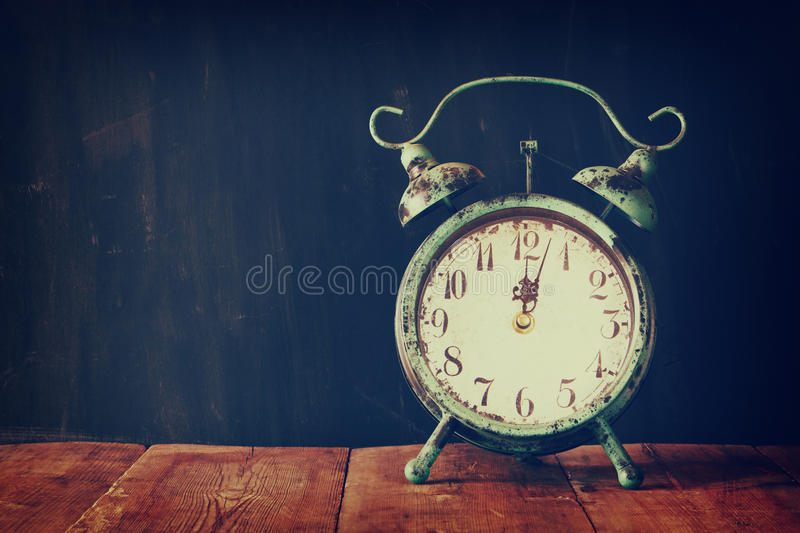 Vintage filtered image of old alarm clock on wooden table in front of black wooden background royalty free stock images