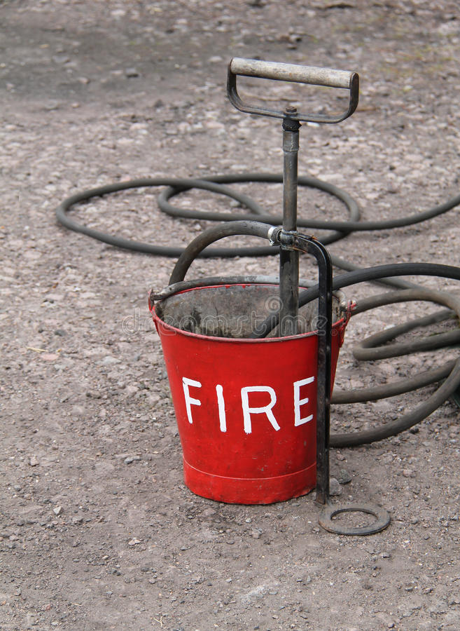 Vintage Fire Bucket. A Vintage Fire Bucket with a Hand Operated Pump royalty free stock photography