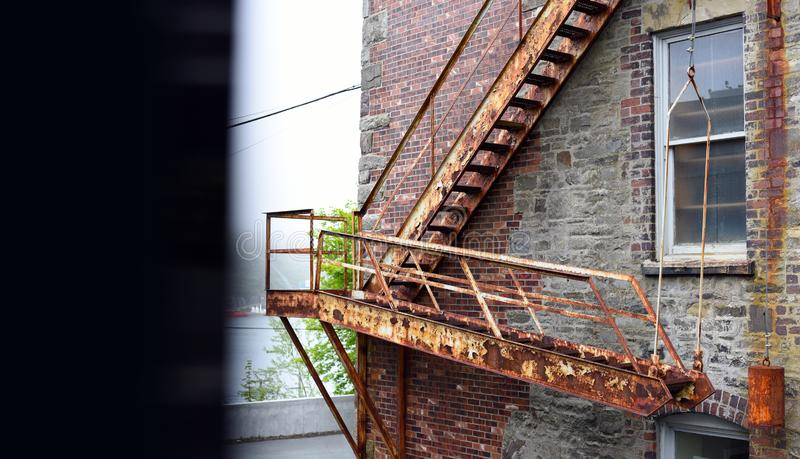Vintage fire escape stairs on brick building stock photo