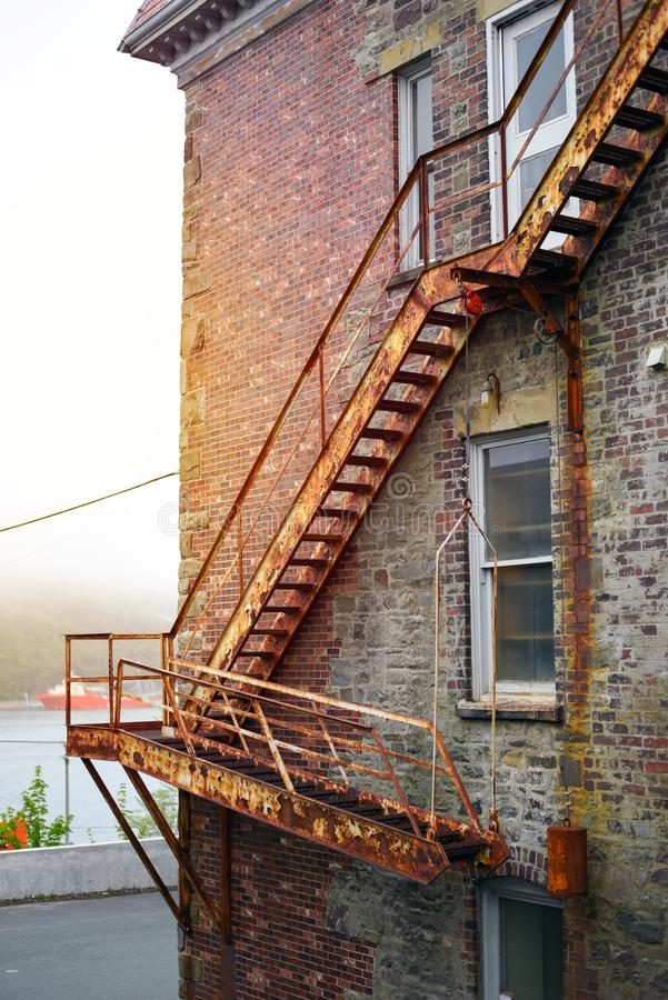 Vintage fire escape stairs on brick building in sunshine stock image