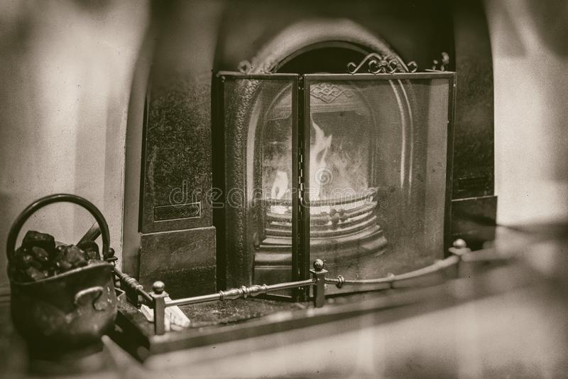 Vintage fireplace with marble surroundings fireside iron black bucket with coal in retro sepia style royalty free stock photo