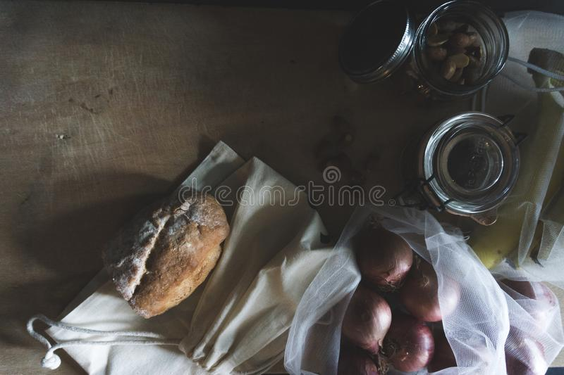 Vintage flat lay look of zero waste containers and food. On a wooden background stock image