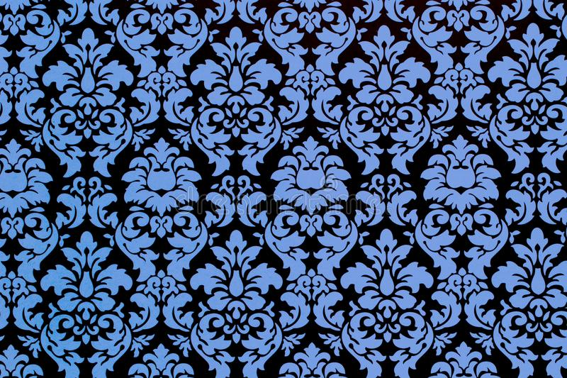 Vintage fleur de lis pattern. A close up of a complex old botanic repeat pattern in shades of black and blue royalty free stock photos