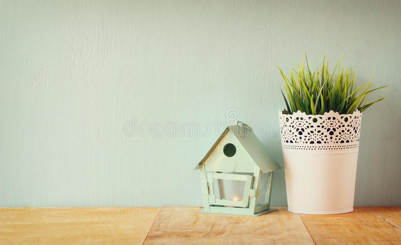 Vintage Flower pot and lantern as a bird house against mint wall and antique lace fabric stock photo
