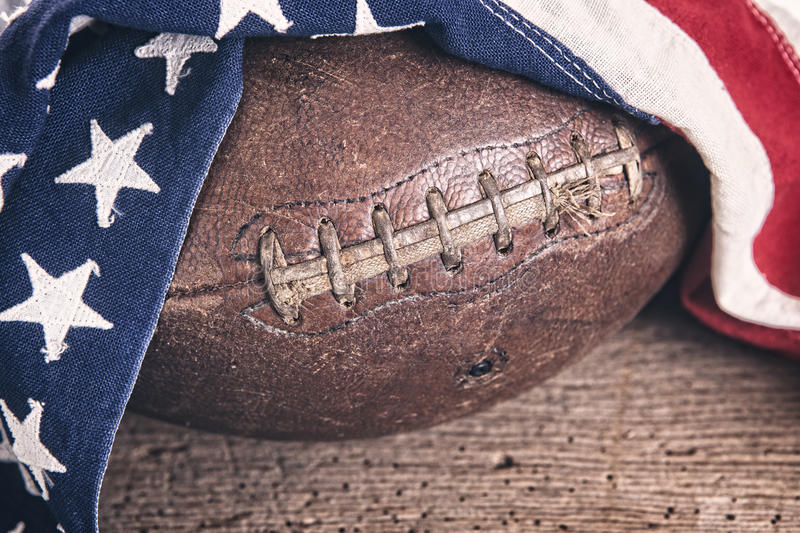 Vintage Football with American Flag. Vintage leather football draped with a vintage American flag on a rustic wooden table with filtered effect royalty free stock images