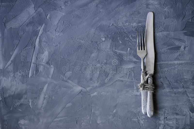 Vintage fork and knife on a concrete backgroun with copy space royalty free stock images