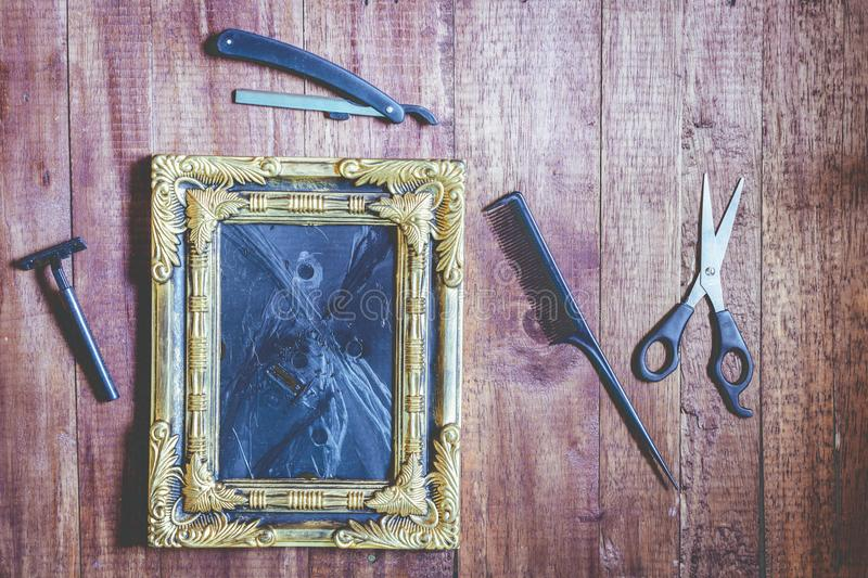 Vintage frame and hairdressing tools on wooden background royalty free stock photography