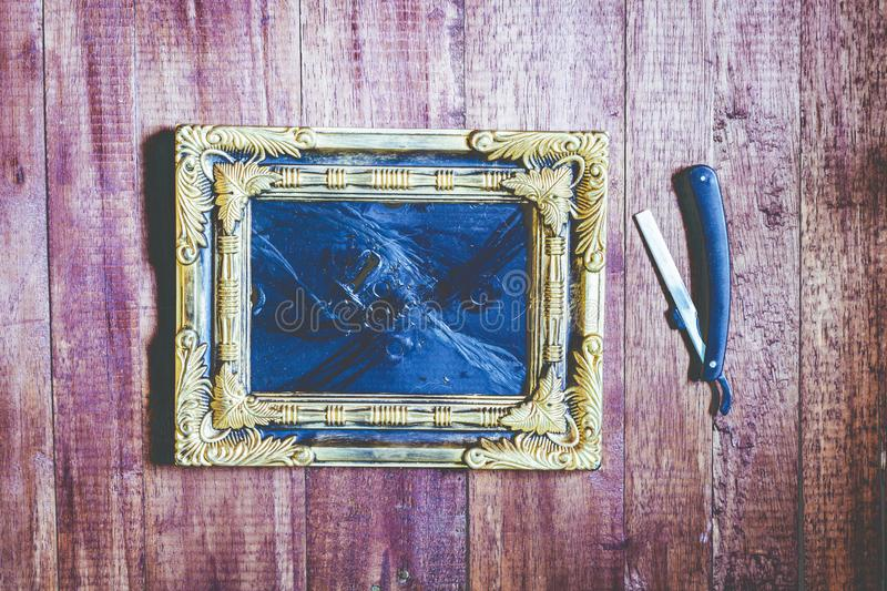 Vintage frame and hairdressing tools on wooden background royalty free stock image